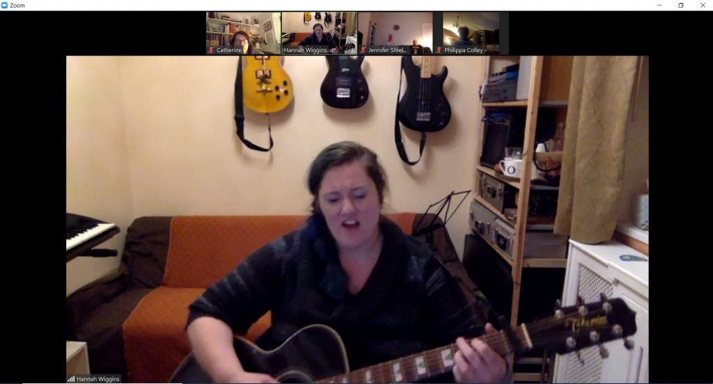 Windows 10 screen showing Hannah singing and playing guitar during an online concert